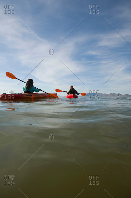 Rear view of young couple in kayaks holding paddles, Great Salt Lake, Utah, USA