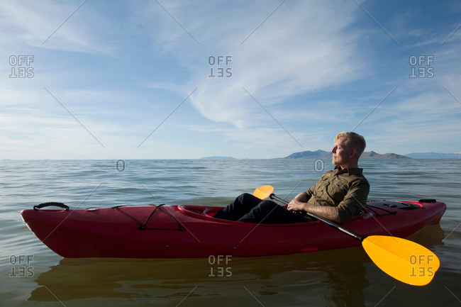 Side view of young man in kayak on water holding paddles, eyes closed, Great Salt Lake, Utah, USA