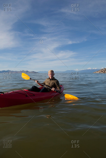 Young man in kayak holding paddles, looking at camera, Great Salt Lake, Utah, USA