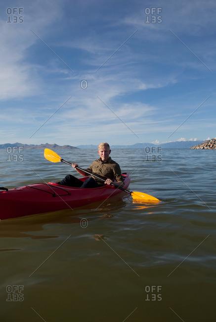 Young man in kayak holding paddles, looking at camera, Great Salt Lake, Utah, USA