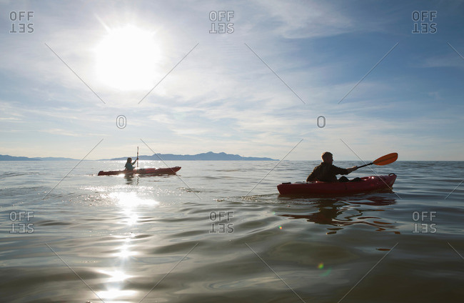 Couple kayaking, sunlight reflecting on water, Great Salt Lake, Utah, USA