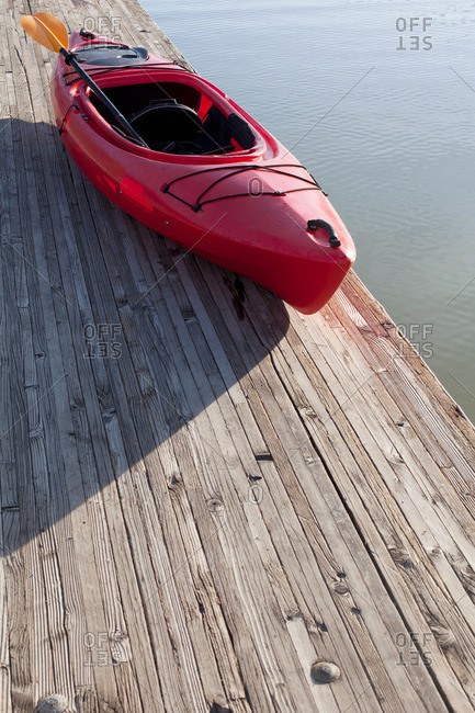 High angle view of kayak and paddle on wooden pier next to water