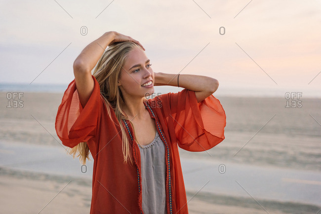 Young woman standing on beach, looking at view