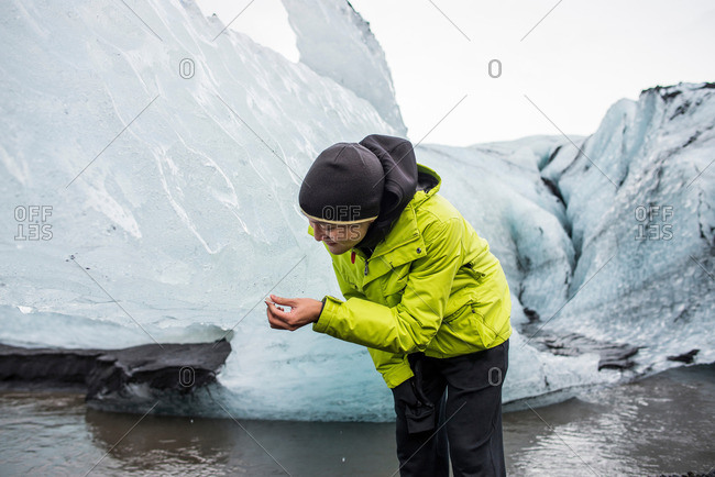 Male tourist looking at ice fragment at Solheimajokull, Iceland