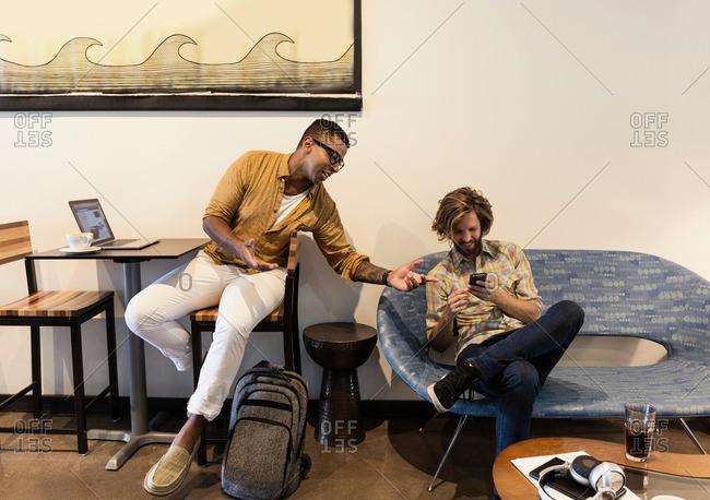 Two men in coffee shop using wireless technology