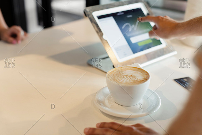 Customer paying for coffee in coffee shop, signing signature on digital transaction technology