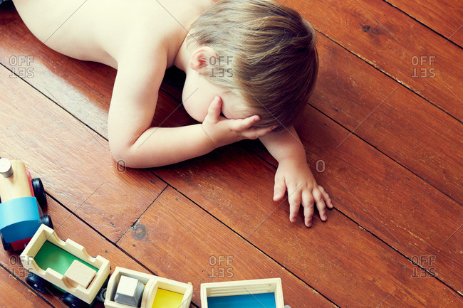 High angle view of boy lying on wooden floor by toy train, head in hand
