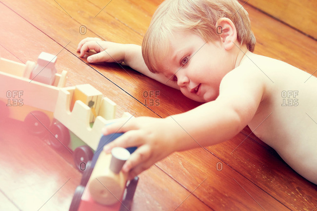 High angle view of boy lying on wooden floor playing with toy train