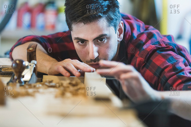 Young man using wood plane to smooth wood object