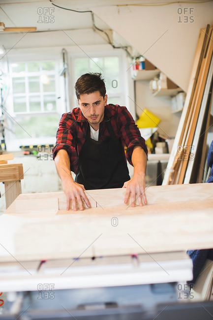 Young man in workshop wearing apron using table saw to cut wood