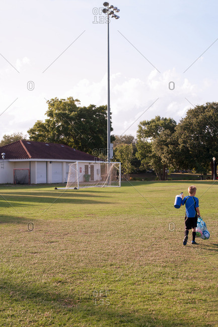 Rear view of boy football player carrying bag of footballs on practice pitch
