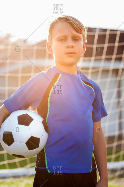 Portrait of boy football player holding football in front of goal