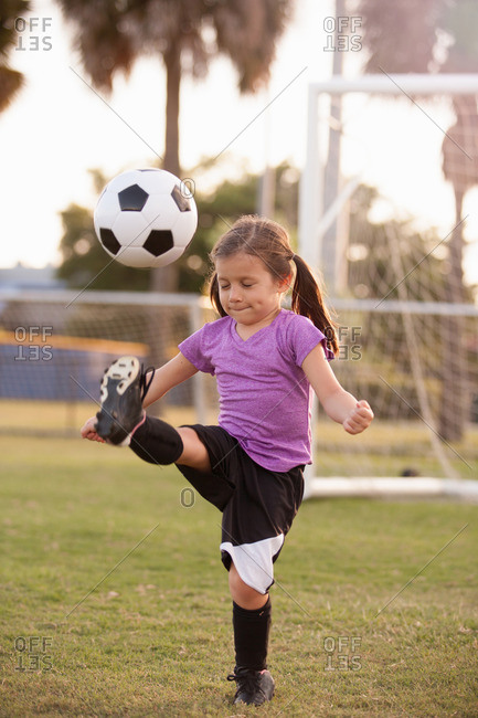 Girl kicking football on practice pitch