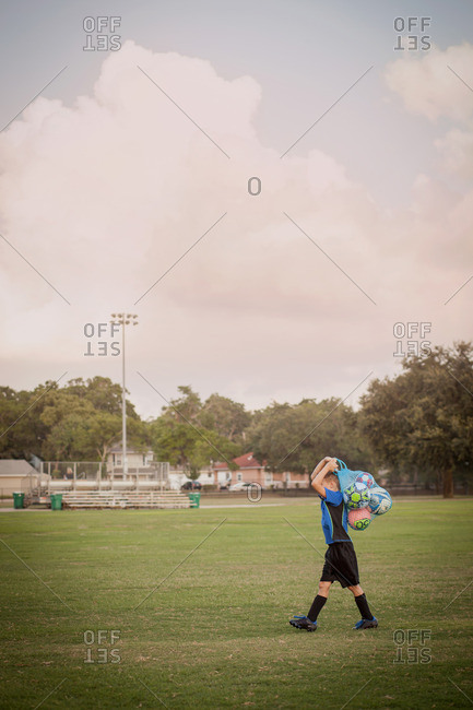 Boy football player carrying bag of footballs on practice pitch