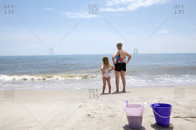 Senior woman with granddaughter with hands on hips looking out from beach