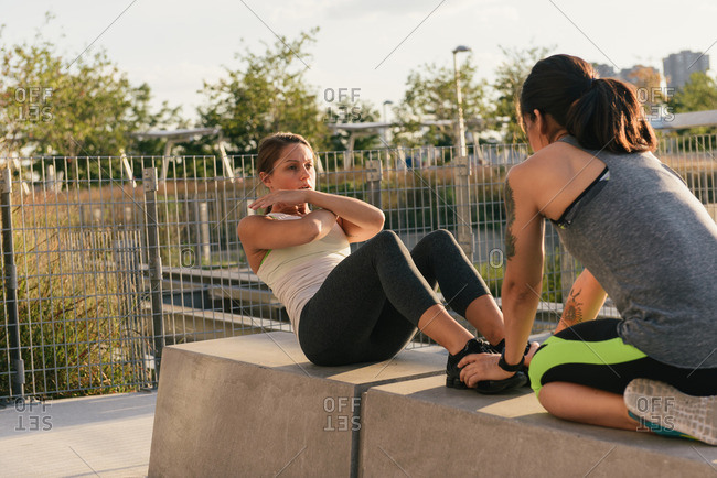 Two friends exercising together and helping to do sit ups