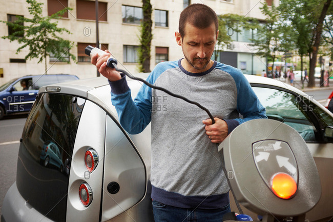 Man charging electric car on street, Paris, France