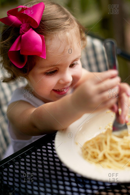 High angle view of girl with pink hair bow sitting at garden eating spaghetti