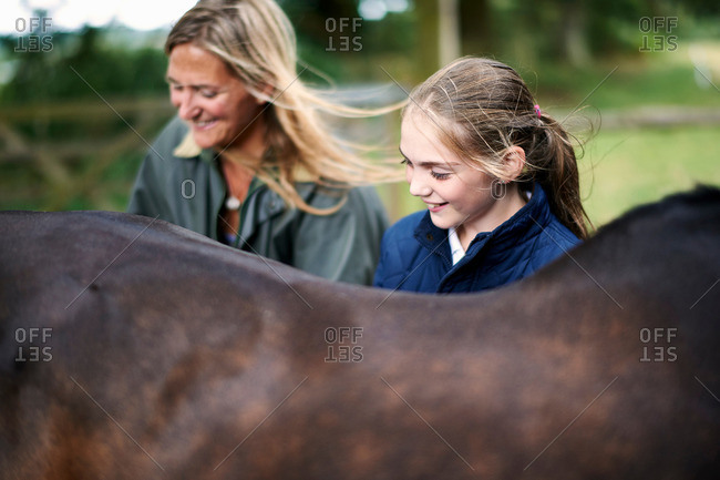 Girl and mother tending horse
