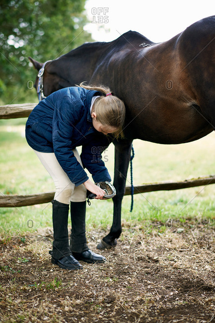 Girl checking horses hoof