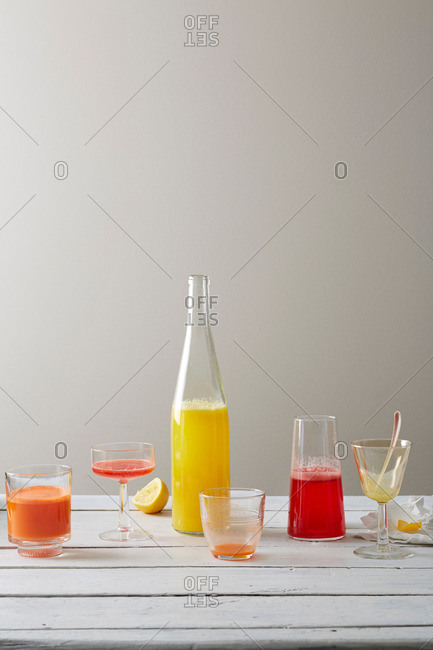 Still life variety of lemongrass lemonade, strawberry rose juice and ginger carrot juice in drinking glasses