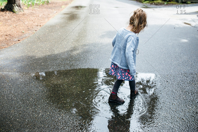 Little girl stomping in a rain puddle