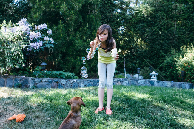 Girl blowing bubbles at a puppy