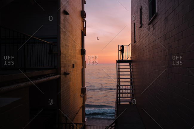 Silhouette of a child standing on a balcony overlooking the ocean
