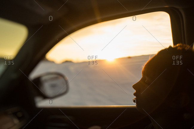 Child sleeping in the passenger seat of a car at sunset