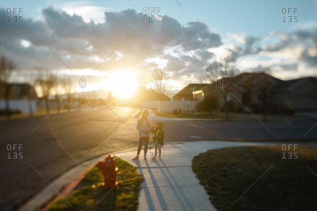 Two girls standing on a street corner in a suburban neighborhood at sunset