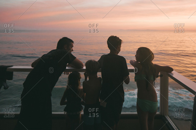Family standing on a balcony together at sunset overlooking the ocean