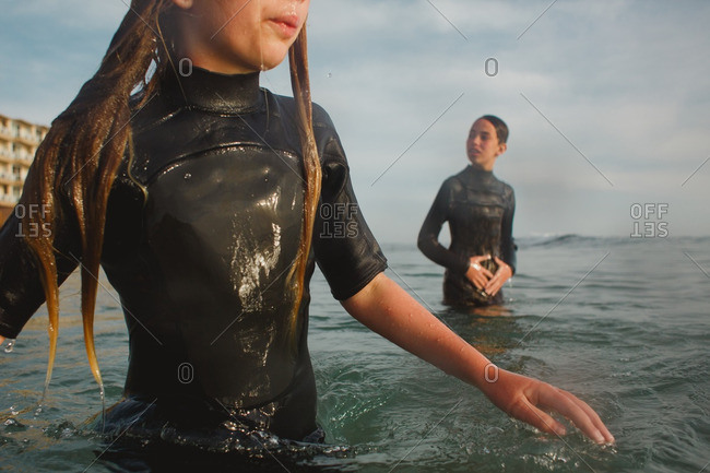 Children wearing wetsuits wade into the ocean together