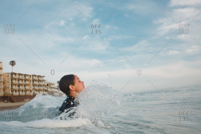 Boy wearing a wetsuit wading into the ocean