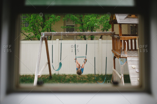 View through an open window of a girl playing on a swing set in her backyard
