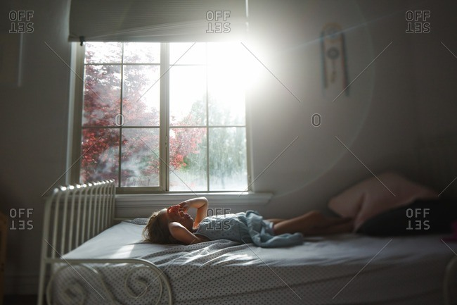 Girl lying down on her bed