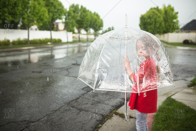 Girl standing on a curb with an umbrella on a rainy day