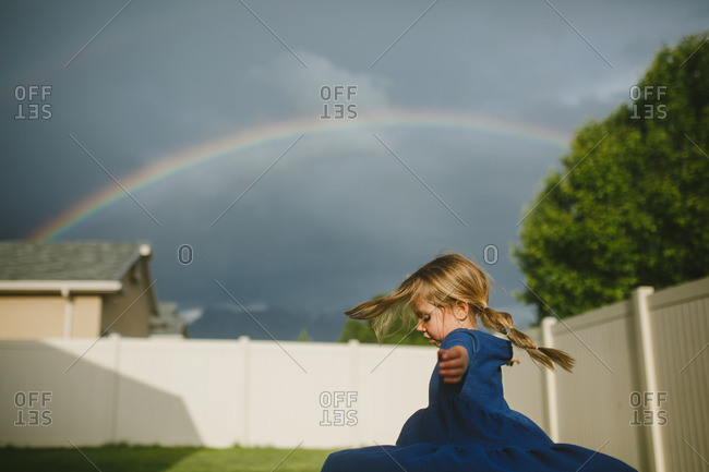 Girl spinning in circles in her backyard under a rainbow
