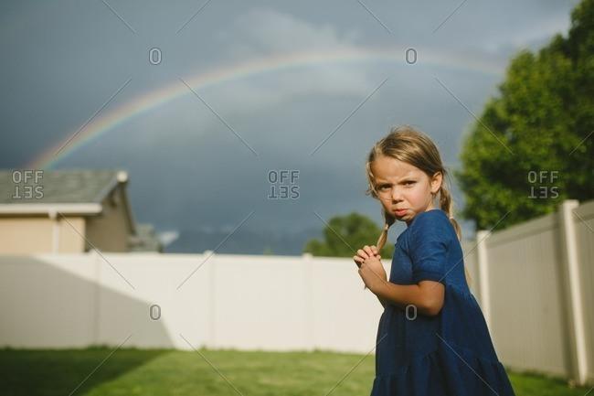 Girl standing in her backyard under a rainbow