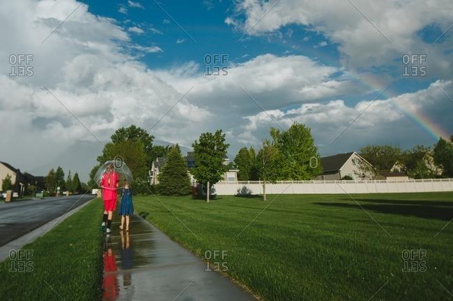 Girls walking with an umbrella along a wet sidewalk under a rainbow