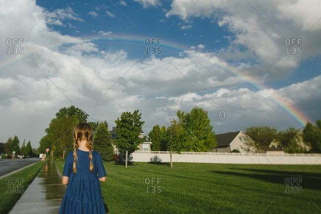 Girl standing on a wet sidewalk under a rainbow