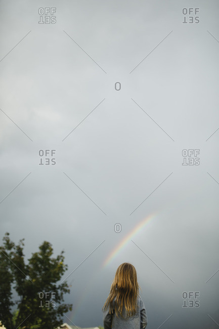 Girl standing outside looking up at a rainbow