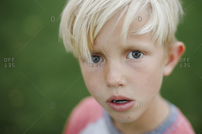 Portrait of a blonde haired boy standing outside in the grass