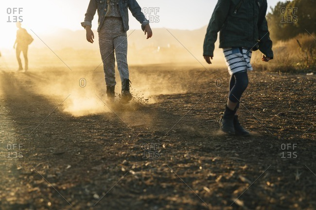 Three people walking down a dirt road together at sunset