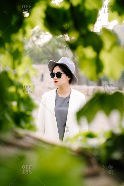 Young Chinese woman between green tree branches