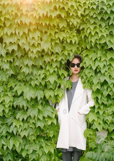 Fashionable Chinese woman leaning into green bushes