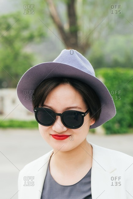 Stylish young Chinese woman in a gray hat and red lipstick