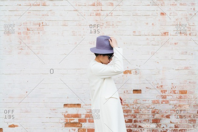 Stylish young Chinese woman in front of a painted brick wall