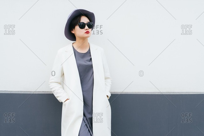 Stylish young woman with a long coat and grey hat