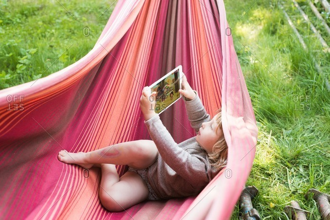 Little girl lying in a hammock playing a game on a digital tablet