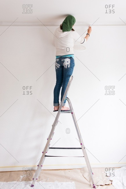 Young woman standing on a ladder painting a wall